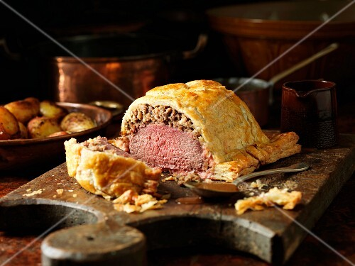 Carved venison Wellington on a chopping board