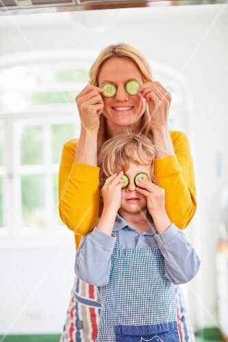A mother and son covering their eyes with cucumber slices