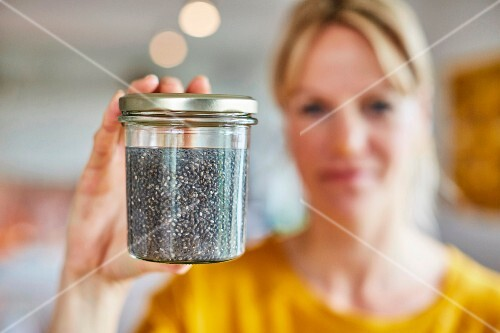 A woman holding a jar of seeds