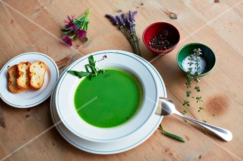 Green herb soup, bread, salt, pepper and fresh herbs