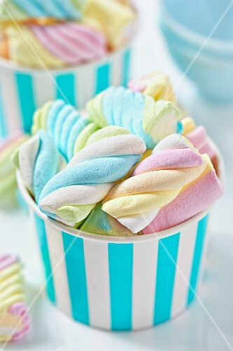 Pastel coloured marshmallows in a striped cup