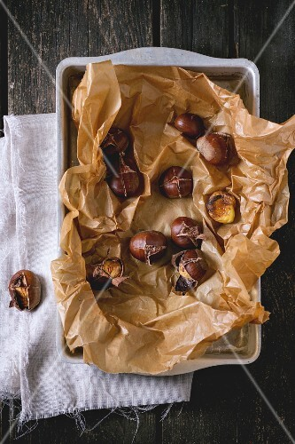 Peeled and unpeeled grilled edible chestnuts on a wooden table (seen from above)