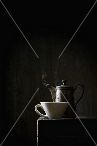 An old coffee pot and a white cup on a black table