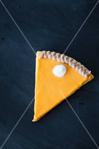 A cookie in the shape of a slice of pumpkin pie with icing