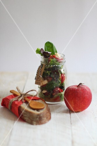Salad in a jar with an apple and a slice of bread