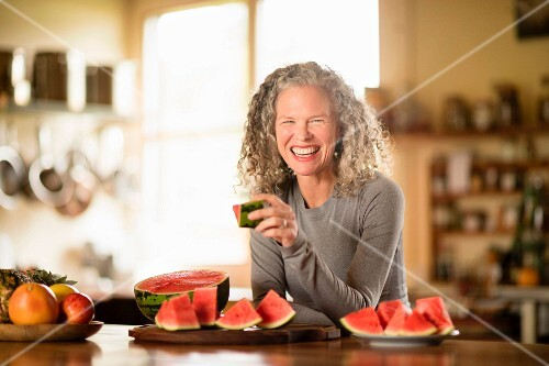 A woman sitting at a dining table eating melon