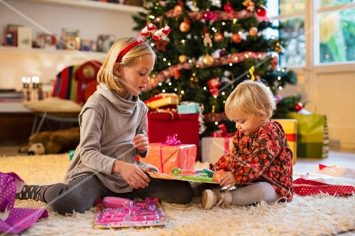 Two children unwrapping Christmas presents in front of a Christmas tree