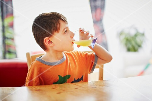 A boy sitting at a table drinking a glass of juice