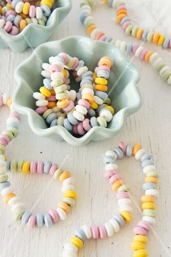Colourful candy necklaces in and next to china bowls