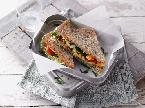 A sandwich with borage, egg and tomatoes in a lunchbox