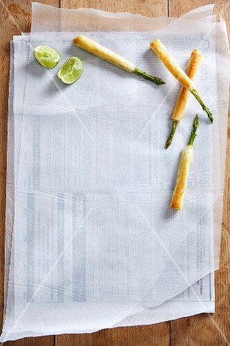 Asparagus spears in filo pastry on a piece of white paper