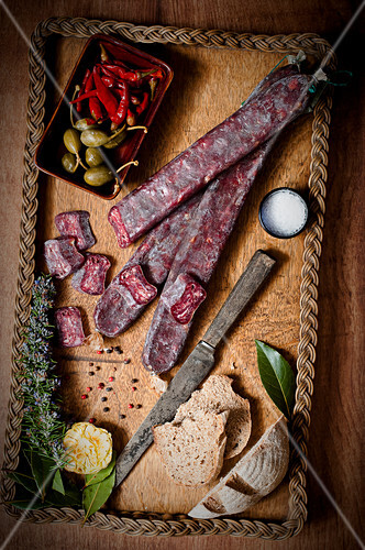 Sliced beef salami on a wooden tray with bread and salt