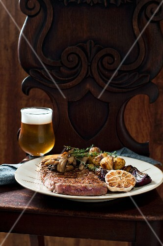 Grilled rib eye steak with red onions, garlic, mushrooms and thyme potatoes