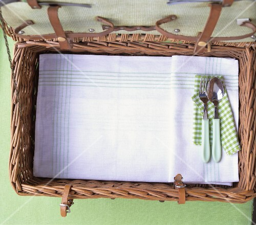 And open picnic basket with cutlery and a tea towel