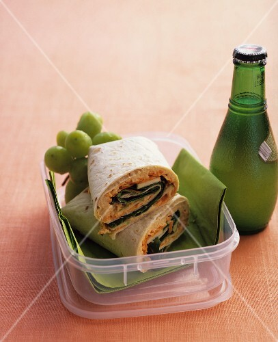 Wraps and grapes in a lunchbox with a bottle of mineral water next to it
