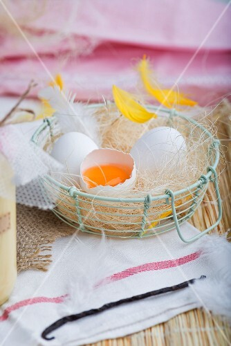 Fresh eggs with feathers in a wire basket