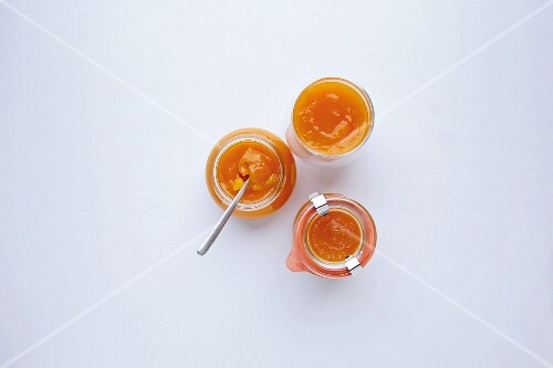 Jars of pumpkin and apricot jam with nutmeg flowers
