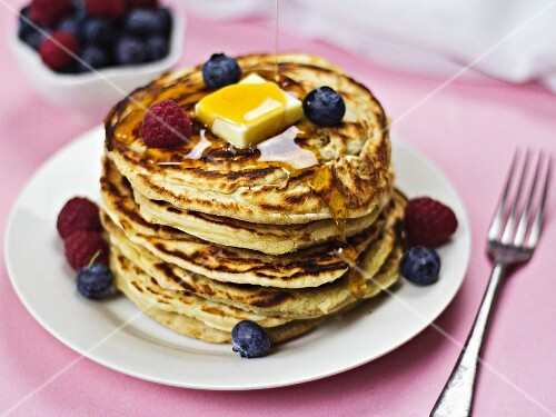 A stack of pancakes with butter, maple syrup and berries