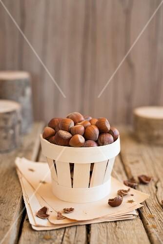 An arrangement of hazelnuts in a wooden basket