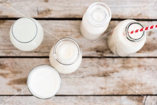 Vegan milk in glass carafes and bottles