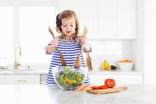A little girl standing at the kitchen table mixing salad