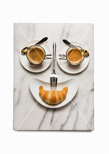 A breakfast face made from coffee cups and a croissant