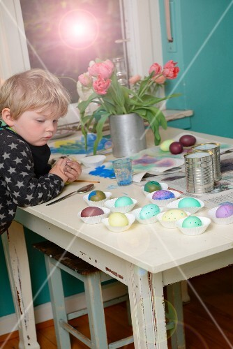 Child next to table looking at painted Easter eggs in paper cake cases