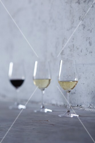 A glass of red wine and two glasses of white wine standing against a stone wall
