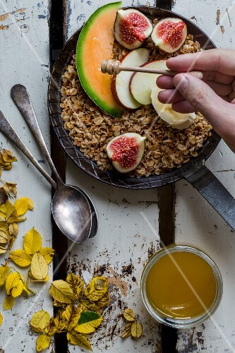 Honey being drizzled over roasted wholemeal oats in a cast-iron pan with fresh fruits