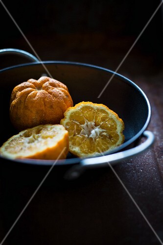 Whole and halved Seville oranges in a black bowl
