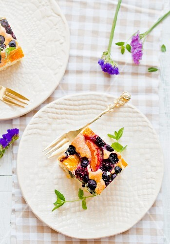 Two pieces of fruit cake on a plate with a silver fork