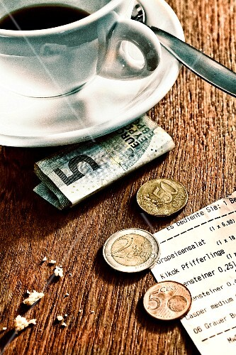 A tip and a receipt next to a cup of coffee