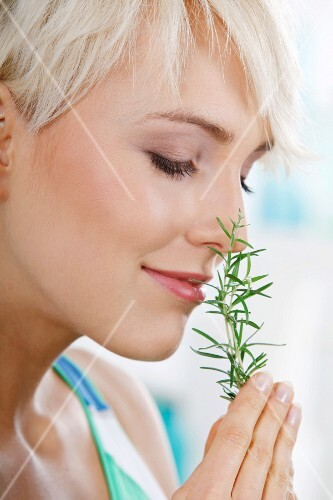 A young blonde woman sniffing a sprig of rosemary