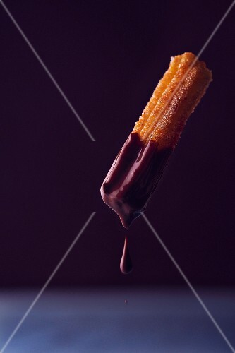 A churro dripping with chocolate