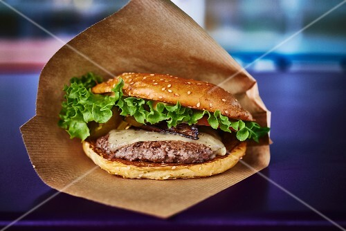 A cheeseburger with salad in a paper bag
