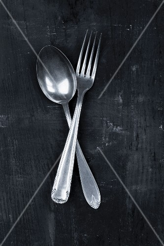 An old spoon and fork on a black surface