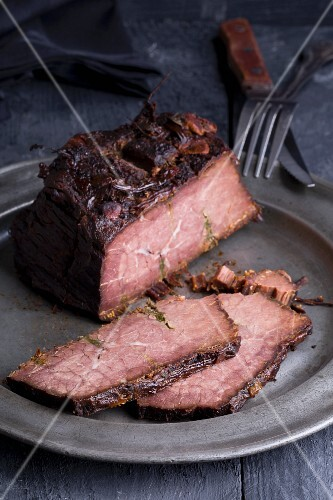 Roast beef studded with rosemary on a pewter plate