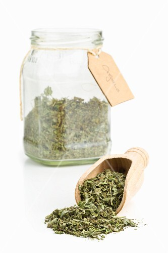 Dried oregano on a wooden scoop and in a storage jar