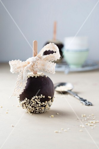 A chocolate coated apple dipped in chocolate almonds