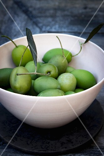 Green olives with stems and leaves in a bowl on a grey wooden tray