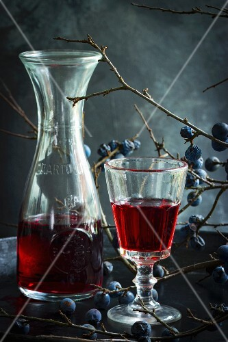 Sloe wine in a glass and a carafe with a sprig of sloes in the background