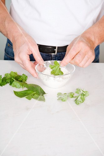 Herb leaves being dusted with flour