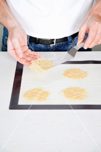 Baked Parmesan chips being removed from a baking tray with a palette knife