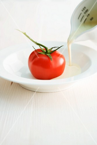 Soup with a stuffed tomato being made