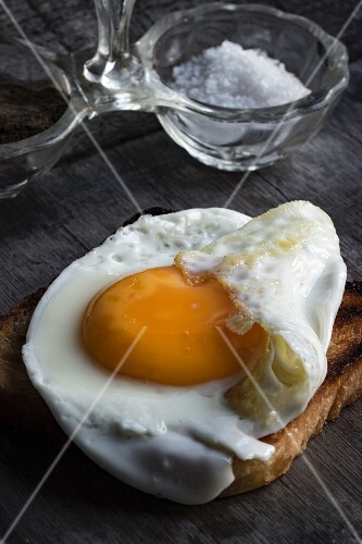 A slice of toast topped with a fried egg with salt and pepper the ground