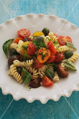 Pasta salad with fresh tomatoes, olives and basil