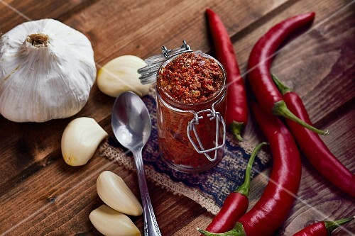 A jar of chilli paste surrounded by ingredients