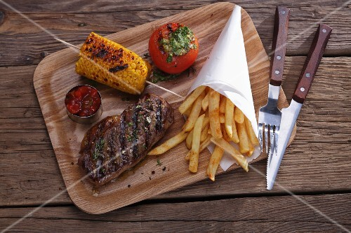 Grilled beef steak with a corn cob and chips on a wooden board