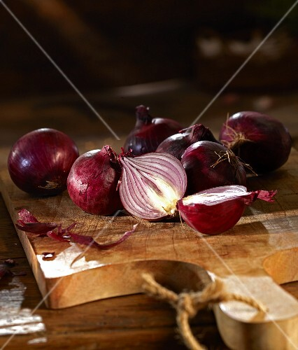 Red onions on a wooden chopping board