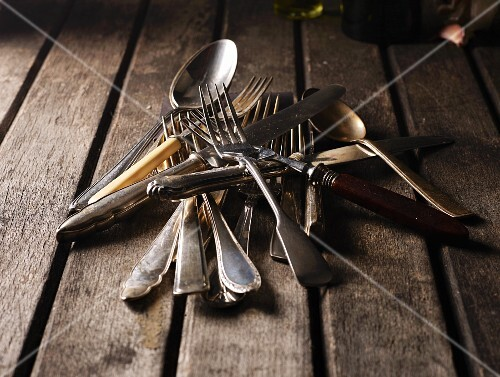Old silver cutlery on a wooden table